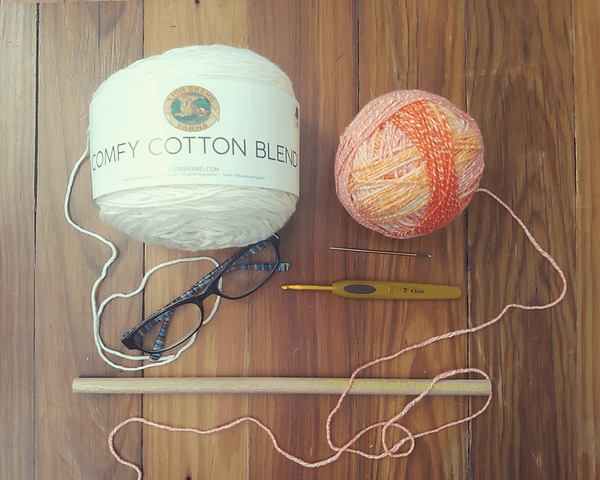 Image of various crochet notions and yarn. Lion brand comfy cotton in whipped cream, lion brand ice cream cotton blend in orange, clover 4.5mm hook, yarn needle, reading glasses and wooden dowel rod. All things used in the Hell. wall art crochet pattern.