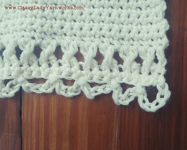 Close up of the bottom border of a crocheted wall tapestry that shows thecrossed double crochet and chain loop stitches used to create the border.