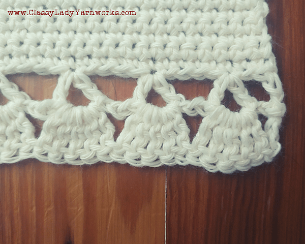 Close up of the bottom border of a crocheted wall tapestry that shows the shell stitches and v stitches used to create the border.