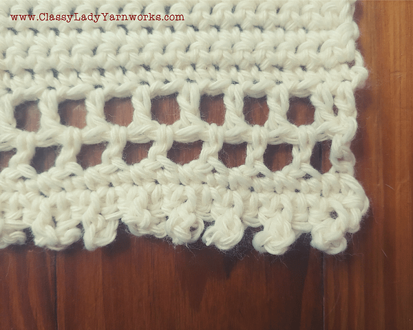 Close up of the bottom border of a crocheted wall tapestry that shows the double crochet and picot stitches used to create the border.