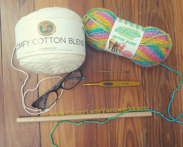 Image of various crochet notions and yarn. Lion brand comfy cotton in whipped cream, lion brand ice cream cotton blend in grape, clover 4.5mm hook, yarn needle, reading glasses and wooden dowel rod. All things used in the Fuck. wall art crochet pattern.
