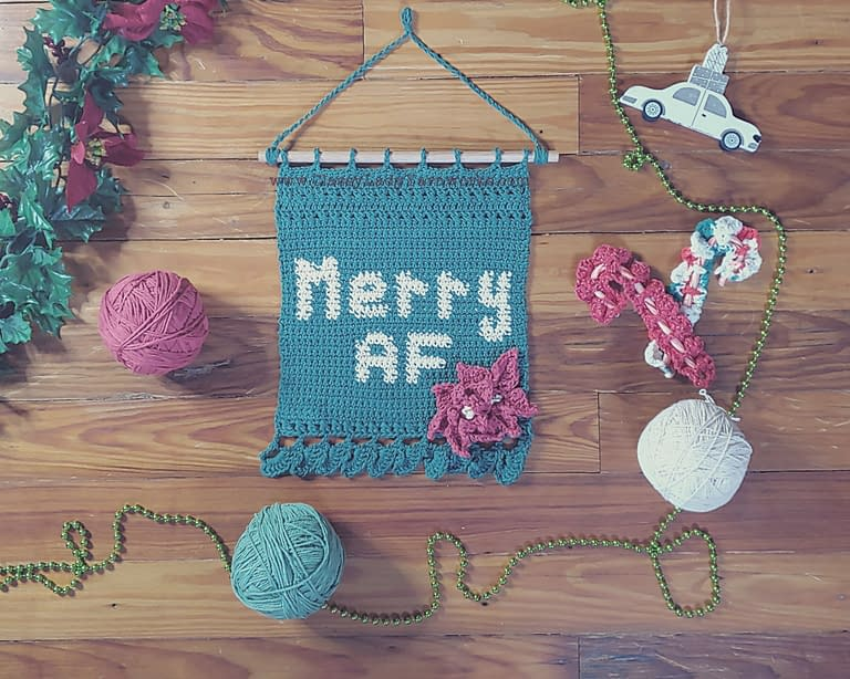 "Finished example of a crochet pattern that says ""Merry AF"" surrounded by various ornaments and balls of yarn in green, red and white. Represents a crochet pattern available at Classy Lady Yarnworks"