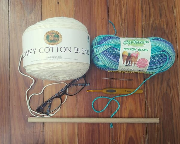 Image of various crochet notions and yarn. Lion brand comfy cotton in whipped cream, lion brand ice cream cotton blend in blueberry, clover 4.5mm hook, yarn needle, reading glasses and wooden dowel rod. All things used in the Damn. wall art crochet pattern.